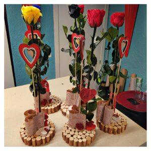 En este base de madera esta presentada tu rosa de San Valentin de color rojo en una forma original.